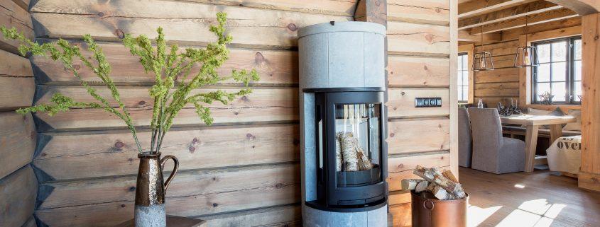 Peis i stuen i en laftet hytte på fjellet