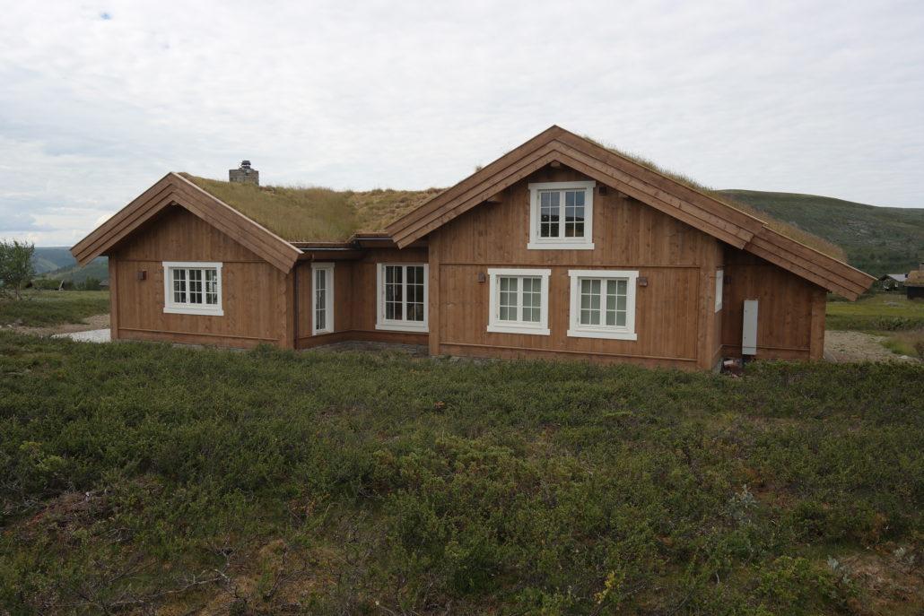 Arkitekttegnet hytte i bindingsverk med torvtak