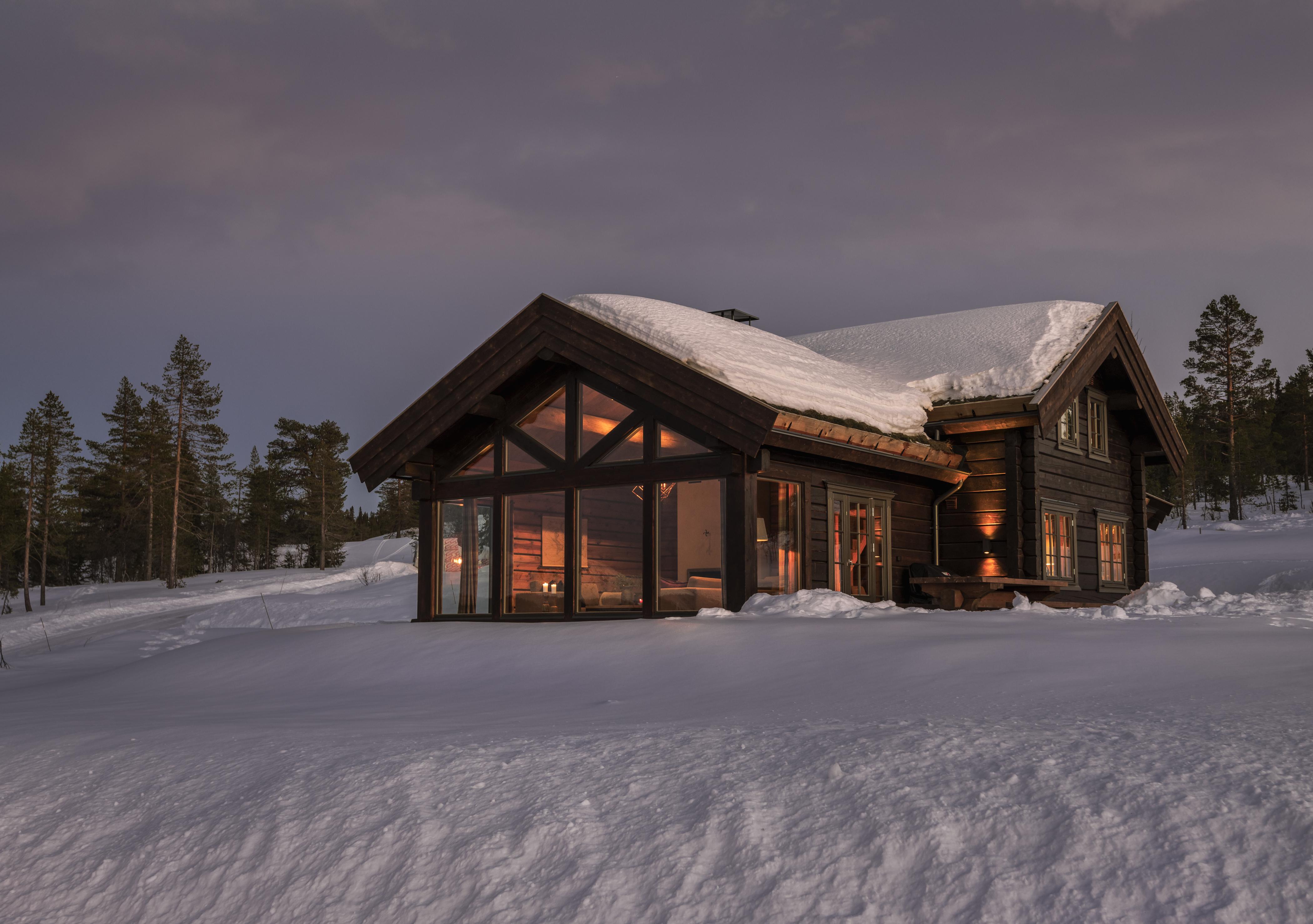 Stor arkitekttegnet fjellhytte med store vinduer i vinter