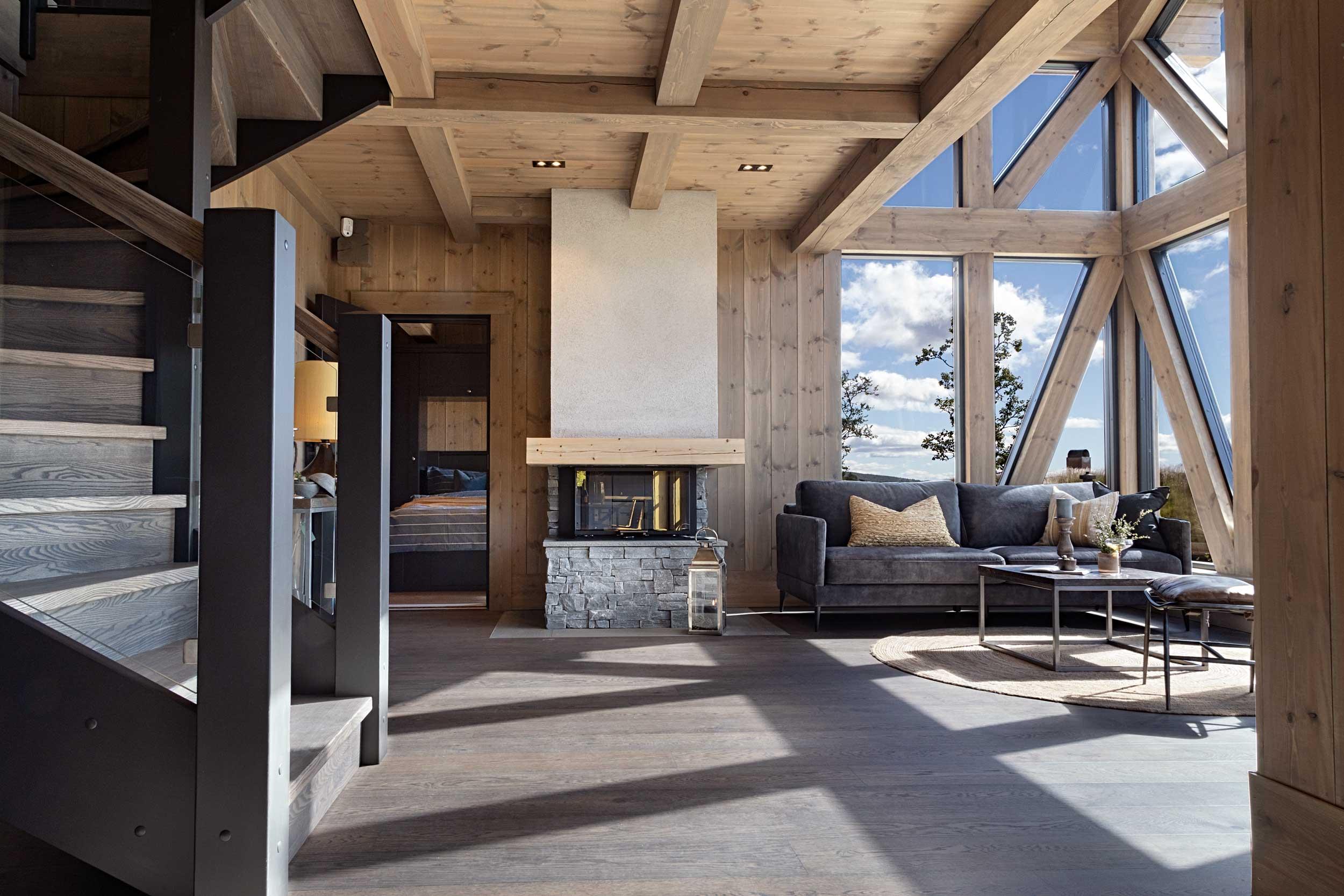 Stue i fjellhytte med store vinduer og peis, bygget av Geilo Laft