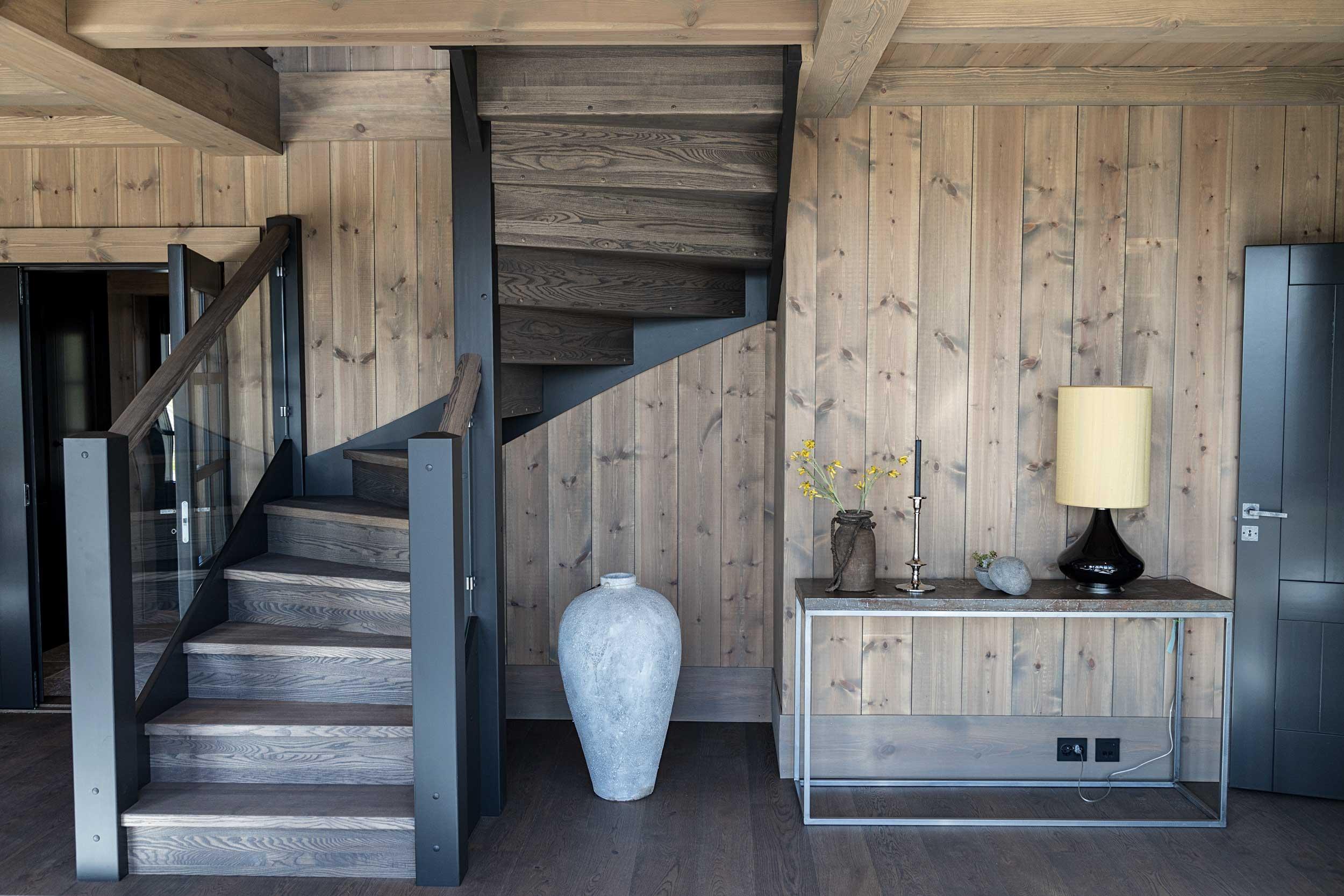 Moderne trapp i nydelig stue i fjellhytte med beisede trevegger, bygget av Geilo Laft.