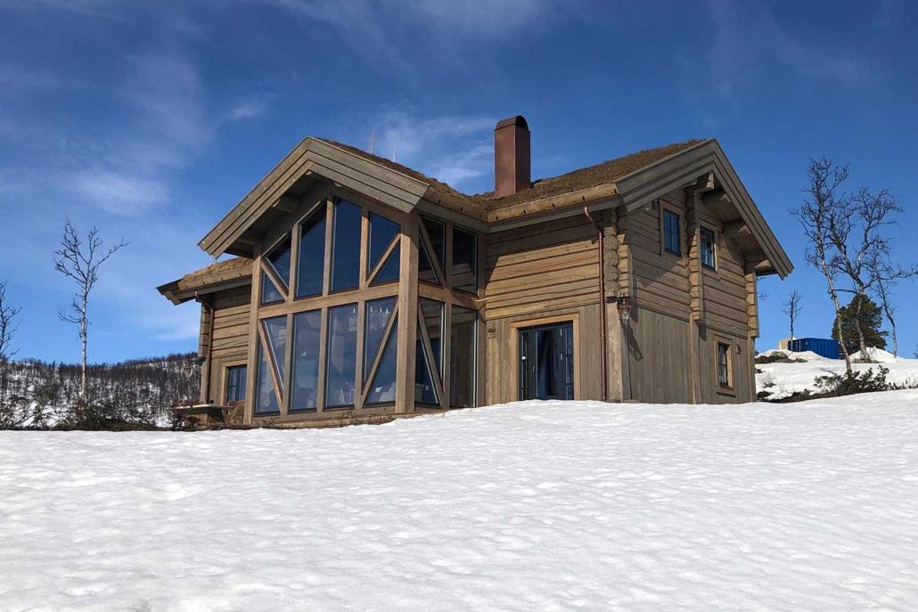 Stavlaft hytte med torvtak og store vinduer i front bygget av Geilo Laft AS. Snø og blå himmel.
