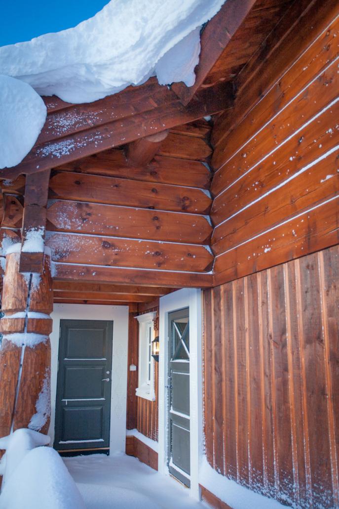 """Inngangsparti av standard hyttemodell """"Kikut"""" bygget av Geilo Laft AS. Vinter og snø."""